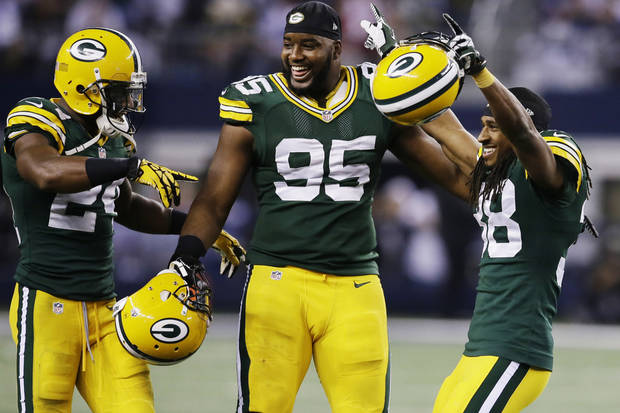 photo - Green Bay Packers cornerback Jarrett Bush (24) defensive end Datone Jones (95) and cornerback Tramon Williams (38) celebrate after beating Dallas Cowboys 37-36 at an NFL football game, Sunday, Dec. 15, 2013, in Arlington, Texas. (AP Photo/Tony Gutierrez)