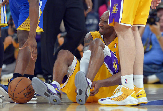 photo - Los Angeles Lakers guard Kobe Bryant grimaces after being injured during the second half of their NBA basketball game against the Golden State Warriors, Friday, April 12, 2013, in Los Angeles. The Lakers won 118-116. (AP Photo/Mark J. Terrill)