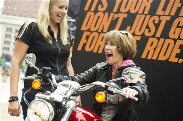 photo - This June 13, 2012 photo shows Harley-Davidson representative Dana Wilke, left, smiling as Nancy Dilley, 68, of Overland Park, Kan., learns the basics while test riding a motorcycle in New York. Harley-Davidson, based in Milwaukee, is the market leader in sales to women. The company travels around the country offering training and safety tips for women. (AP Photo/Charles Sykes)