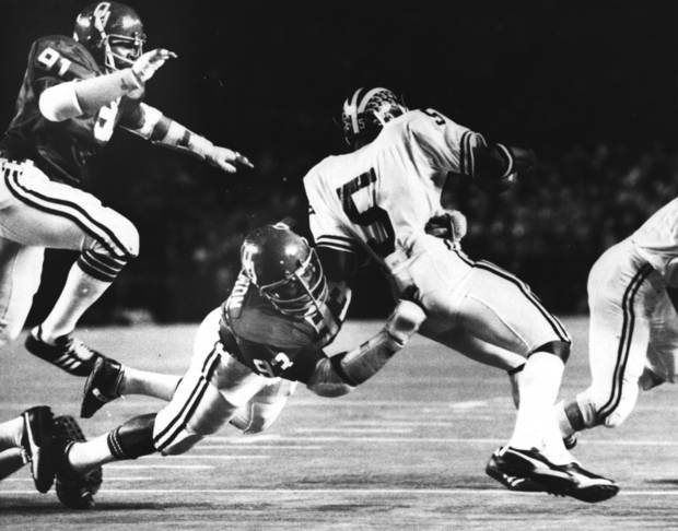 photo - OU defensive lineman Lee Roy Selmon puts the stop on Michigan quarterback Rick Leach during the Orange Bowl classic on 1/1/76 in Miami, FL. That's broher Dewey Selmon at upper left. OU beat the Michigan Wolverines that night by a 14-6 score. Staff photo by J. Pat Carter taken 1/1/76.