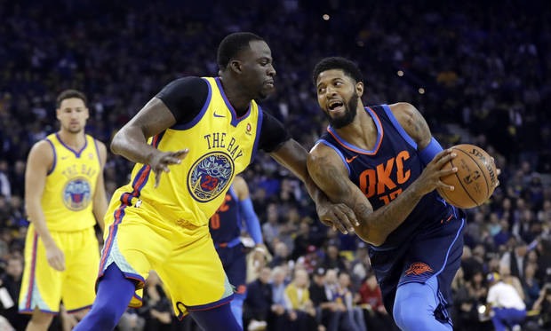 Oklahoma City Thunder's Paul George, right, is defended by Golden State Warriors' Draymond Green during the first half of an NBA basketball game Saturday, Feb. 24, 2018, in Oakland, Calif. (AP Photo/Marcio Jose Sanchez)