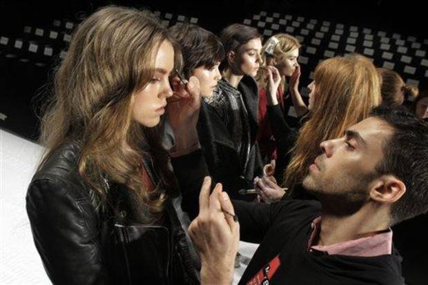 photo - FILE - In this Feb. 15, 2012, file photo, models have their make-up finalized under runway light before the J. Mendel Fall 2012 collection is modeled during Fashion Week, in New York.  The 19 editors of Vogue magazines around the world made a pact to project the image of healthy models. They agreed to