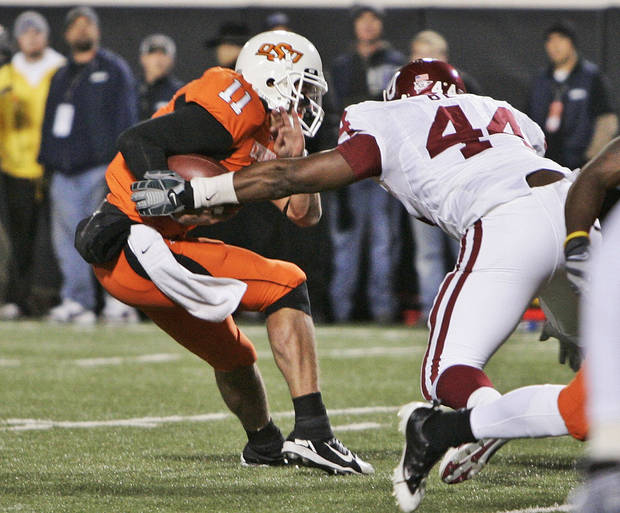 photo - Oklahoma defensive end Jeremy Beal, right, tackled Oklahoma State quarterback Zac Robinson, left, and forces a fumble in the third quarter of an NCAA college football game in Stillwater, Okla., Saturday, Nov. 29, 2008. (AP Photo/Sue Ogrocki)
