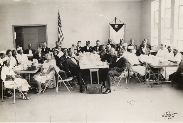 Men and women are seated for a Mason's dinner.