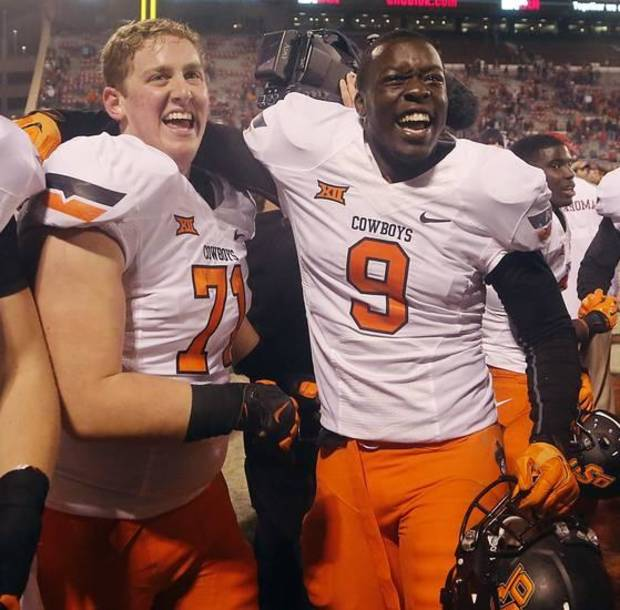 Cowboys Brad Lundblade (71) and Gyasi Akem (9) celebrate after their 38-35 overtime win in Bedlam last year in Norman. (Photo by Chris Landsberger)