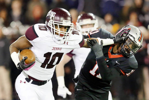 photo - Jenks' Steven Parker pushes off Union's Robert Thomas on a gain during Thursday night's 6A title game.  Photo by MICHAEL WYKE, Tulsa World