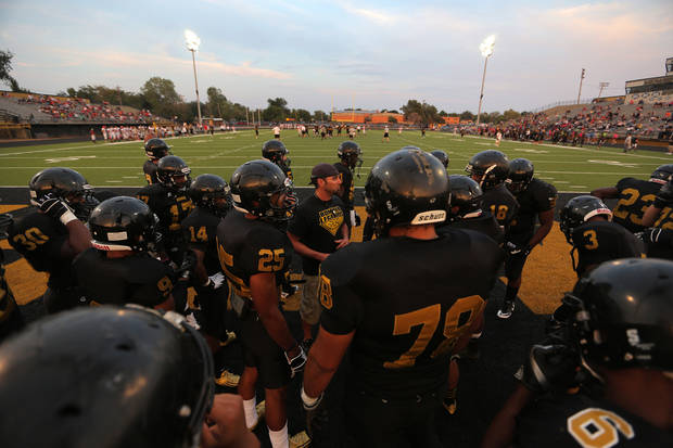 photo - HIGH SCHOOL FOOTBALL: Midwest City lines up for warm-ups during a scrimmage between Midwest City and Carl Albert at Bomber Stadium in Midwest City, Thursday, Aug. 23, 2012.  Photo by Garett Fisbeck, For The Oklahoman