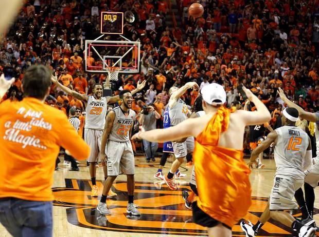 Oklahoma State's Michael Cobbins (20), Jeff Newberry (22) and Phil Forte III (13) celebrate as fans rush the court following the men's college basketball game between Oklahoma State University and the University of Kansas at Gallagher-Iba Arena in Stillwater, Okla., Saturday, Feb. 7, 2015. OSU won 67-62. Photo by Sarah Phipps, The Oklahoman