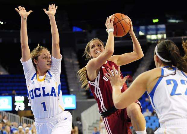 photo - Oklahoma guard Morgan Hook, center, attempts to get by UCLA guard Thea Lemberger (1) and guard Madeline Brooks (22) during the second half of an NCAA college basketball game, Sunday, Nov. 24, 2013, in Los Angeles. UCLA won 82-76. (AP Photo/Gus Ruelas)