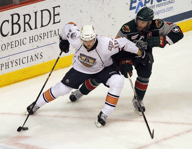 photo - OKC's Teemu Hartikainen (10) skates against Houston's Drew Bagnall (4) during a game between the Oklahoma City Barons and the Houston Aeros at the Cox Convention Center in Oklahoma City, Sunday, April 22, 2012.  Photo by Garett Fisbeck, For The Oklahoman