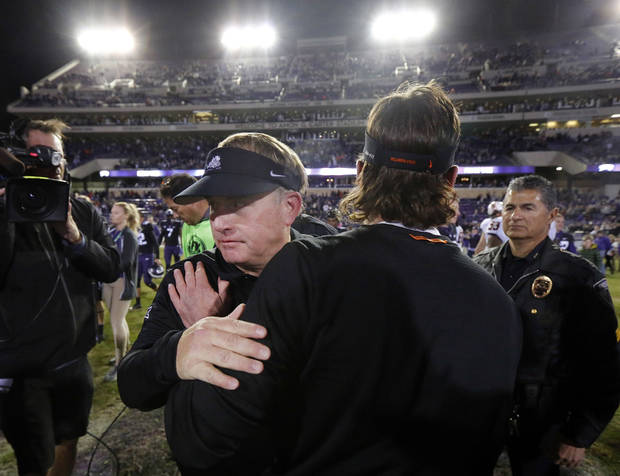 TCU coach Gary Patterson, front left, is congratulated on the TCU win by Oklahoma State coach Mike Gundy following an NCAA college football game in Fort Worth, Texas, Saturday, Nov. 24, 2018. TCU won 31-24. (Tom Fox/The Dallas Morning News via AP)