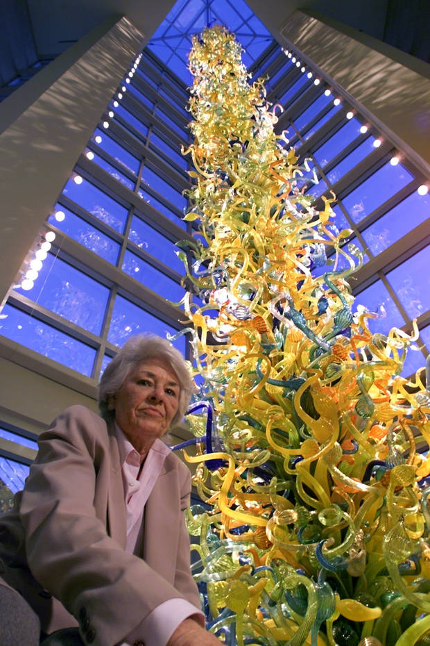 The late Carolyn Hill, who was the longtime executive director of the Oklahoma City Museum of Art, is dwarfed by the 55-foot towering blown-glass sculpture by Seattle Artist Dale Chihuly that has become the signature piece of the museum's downtown OKC home, which opened in 2002. [The Oklahoman Archives]