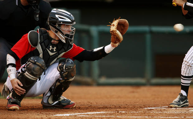 photo - Yukon's Jon Denney catches during a high school baseball game at the Chickasaw Bricktown Ballpark in Oklahoma City, Thursday, March 14, 2013. Photo by Bryan Terry, The Oklahoman