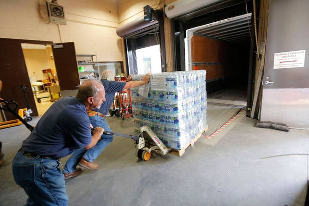 Southern Baptist Disaster Relief volunteers Dale Price (left) and Serge Renard, load a pallet of water headed for South Carolina to aid survivors of historic flooding in the state and neighboring North Carolina. [Photo by Susan Whitley]