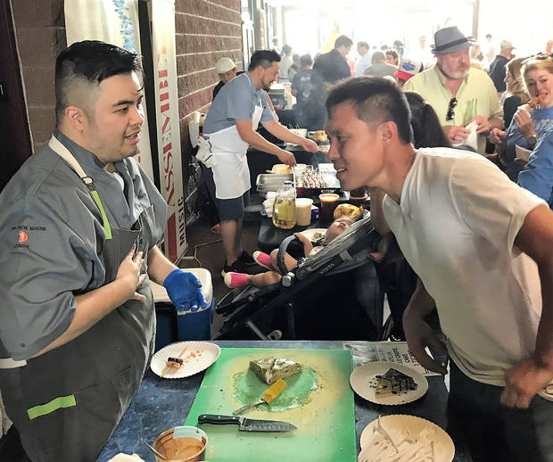 Chef Danh Do explains his dish to a guest at the Asian Food Fair. [Dave Cathey/The Oklahoman]