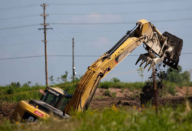 photo - A backhoe cleans out an old pond at the Cushing Superfund sight. Clean up is taking place at the Cushing, Okla Superfund site on Tuesday June 22, 2009. Photo by Mitchell Alcala, The Oklahoman ORG XMIT: KOD