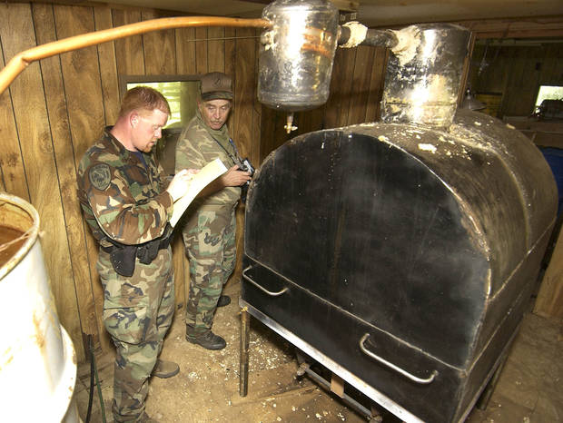 photo - ABLE Commission agents Kent James and Joe Cantrell take note of the contents of a trailer after agents make a raid on this McCurtain County property and discover a large alchohol still.  Staff photo by Paul Hellstern.