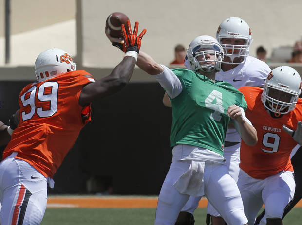 photo - Oklahoma State quarterback J.W. Walsh (4) throws under pressure from defensive tackle Calvin Barnett (99) and defensive end Jeremiah Tshimanga (9) during the Oklahoma State spring NCAA college football game in Stillwater, Okla., Saturday, April 20, 2013. (AP Photo/Sue Ogrocki)