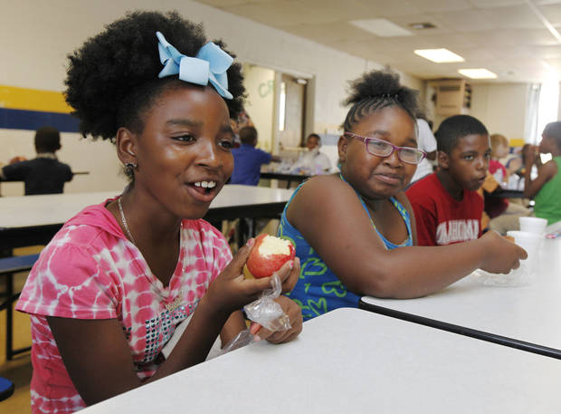 photo -  Carli Johnson, left, Quania Swait and Makale Smith enjoy lunch Monday at Crutcho School, 2401 N Air Depot Blvd., one of 11 feeding sites that are part of the Oklahoma Summer Food and Education Program, a new pilot program offered by Feed The Children in partnership with the U.S. Department of Agriculture. Photo by Paul Hellstern, The Oklahoman   PAUL HELLSTERN