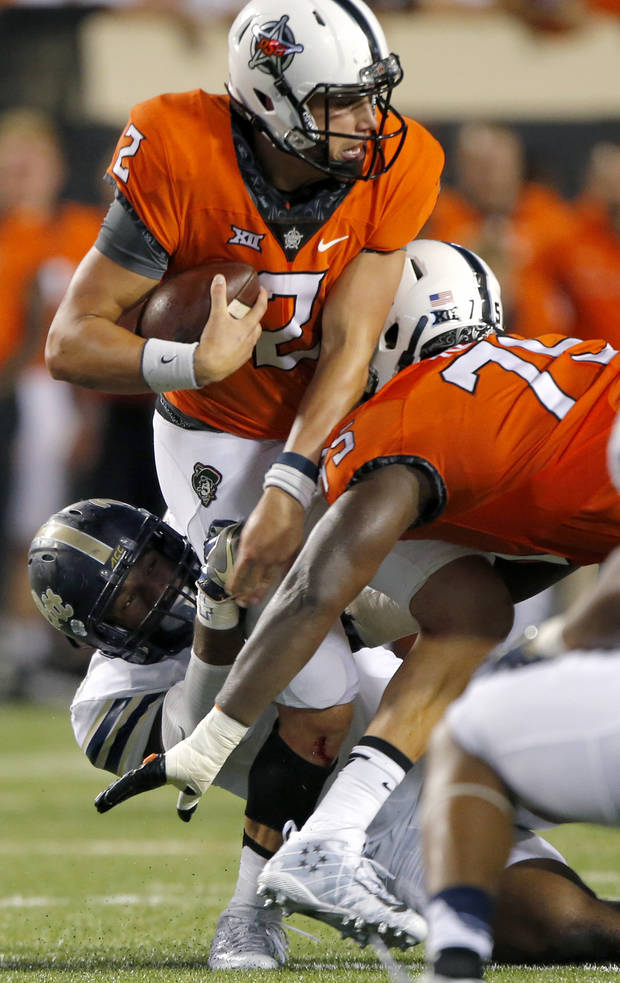 Oklahoma State's Mason Rudolph (2) is sacked by Pittsburgh's Ejuan Price (5) during a college football game between the Oklahoma State Cowboys (OSU) and the Pitt Panthers at Boone Pickens Stadium in Stillwater, Okla., Saturday, Sept. 17, 2016. Photo by Chris Landsberger, The Oklahoman