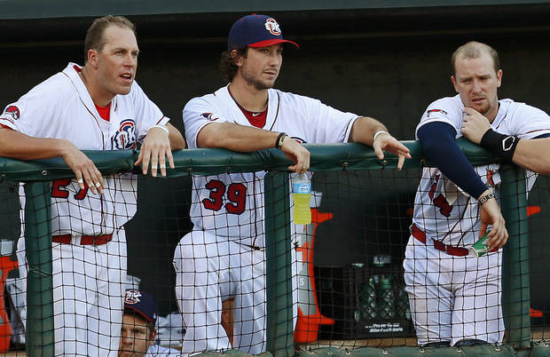 photo - Oklahoma CIty's Brett Wallace, center, talks with Mike Hessman, left, and Chris Wallace during the RedHawks minor league baseball game against the Iowa Cubs at the Chickasaw Bricktown Ballpark in Oklahoma City, Wednesday, July 25, 2012. Photo by Bryan Terry, The Oklahoman