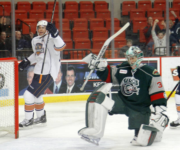 photo - CELEBRATION: Josh Green of the Oklahoma City Barons celebrates beside Houston Aeros goalie Matt Hackett after scoring during an AHL hockey game at the Cox Convention Center in Oklahoma City, Friday, Jan. 27, 2012. Photo by Bryan Terry, The Oklahoman