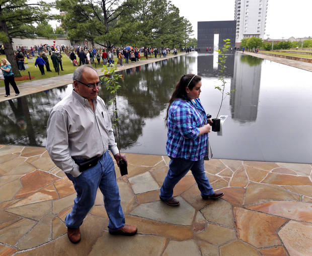 <p>Louis Hernandez and his daughter, Sarah Hernandez, carry seedlings from the Survivor Tree on Tuesday at the Oklahoma City National Memorial & Museum after the 21st anniversary remembrance ceremony. Sarah survived the bombing in the YMCA day care center across the street.</p>