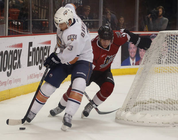 photo - Brandon Davidson of the Oklahoma City Barons tries to get past Mark Olver of the Lake Erie Monsters during AHL hockey game at the Cox Convention Center in Oklahoma City, Tuesday, October 23, 2012. Photo by Bryan Terry, The Oklahoman