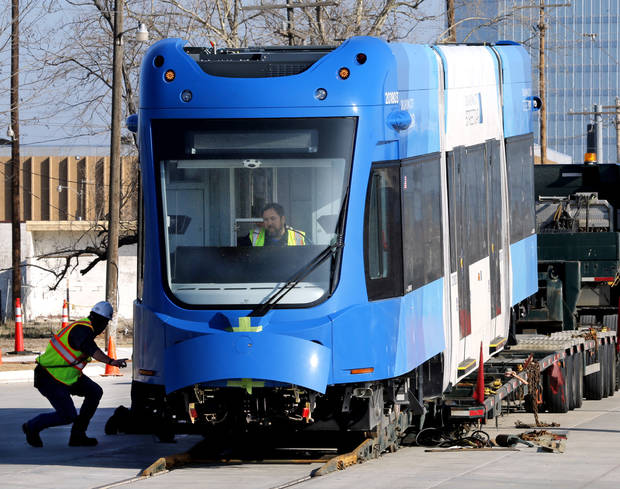 Streetcars are rolled off a long flatbed for delivery to the Oklahoma City streetcar maintenance facility. Monday's delivery was the third of seven on Oklahoma City's initial order of Liberty streetcars. [Photo by Steve Sisney, The Oklahoman]