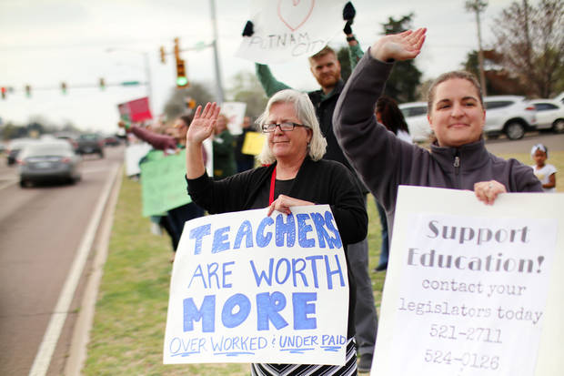 Cynthia Mize, Harvest Hills Elementary, left, and Samantha VanOsdol, Dennis Elementary, hold signs and wave as teachers rallied at N.W. Expressway and North Meridian during rush hour traffic in Oklahoma City, Thursday, March 29, 2018. Photo by Doug Hoke, The Oklahoman