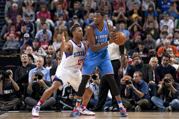 photo - Oklahoma City Thunder's Kevin Durnat, right, keeps the ball from Philadelphia 76ers' Evan Turner during their NBA preseason basketball game at the Phones4 u Arena in Manchester, England, Tuesday, Oct. 8, 2013. (AP Photo/Jon Super) ORG XMIT: MJS104