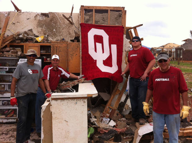 photo - Oklahoma assistant Jay Norvell, athletic director Joe Castiglione, football player Bronson Irwin and assistant Tim Kish helped out in the Heatherwood neighborhood of Moore on Saturday. Among the things found in the rubble was an OU flag. PHOTO PROVIDED BY OU SPORTS INFORMATION