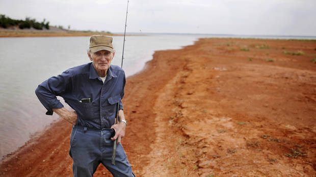 photo - Angler Joe Myers stands in the reddish silt that until recent years was the bottom of Canton Lake. Myers had been casting in a shallow strip of water near the dam on Wednesday, May 21, 2014, when this photo was taken. He says the water depth where he is standing should be between 8 and 10 feet when the lake is at its normal levels. A sustained drought combined with the release of millions of gallons of water downstream to Oklahoma City in 2013 has caused large sections of the lake to dry up and has extended the lake's shoreline by hundreds of feet.   Photo by Jim Beckel, The Oklahoman