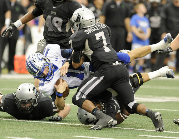 photo - Georgetown quarterback Jake Hubenak (10) is tackled by a group of Denton Guyer defenders, including Terrell Singleton (7), in the first half during the UIL Class 4A Division I high school football championship game, Saturday, Dec. 22, 2012, in Arlington, Texas. (AP Photo/Matt Strasen)