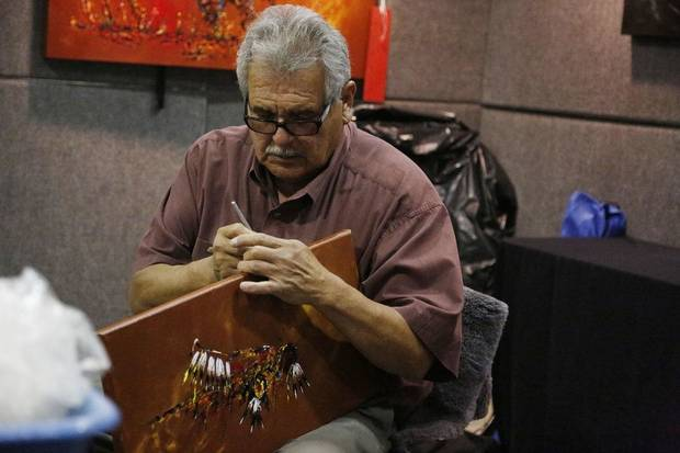 Clancy Gray, 2019 Red Earth Honored One, works in his booth during the first day of the 2019 Red Earth Festival at the Cox Convention Center in Oklahoma City. [The Oklahoman Archives]