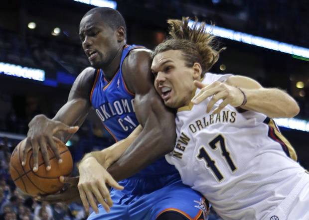 photo - Oklahoma City Thunder power forward Serge Ibaka battles for a rebound with New Orleans Pelicans power forward Lou Amundson (17) in the second half of an NBA basketball game in New Orleans, Friday, Dec. 6, 2013.  The Thunder won 109-95. (AP Photo/Gerald Herbert)
