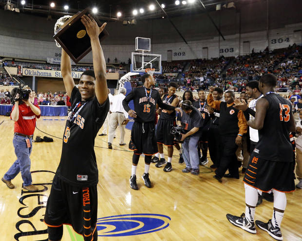 photo - Douglass's Stephen Clark carries the championship trophy after his 51-point scoring run during the 4a boys championship game where the Douglass high school Trojans defeated the Roland Rangers 82-80 at the State Fair Arena on Saturday, March 9, 2013 in Oklahoma City, Okla. PHOTO BY STEVE SISNEY, The Oklahoman <strong>STEVE SISNEY</strong>