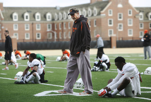 "photo - Oklahoma State defensive coordinator Glenn Spencer walks through rows of players stretching during practice on Tuesday, April 1, 2014 at the outside fields of the Sherman E. Smith training facility of Oklahoma State University in Stillwater. The Cowboys' will hold ""Orange Blitz"", an open practice that will replace the annual spring game this Saturday. Photo by KT King/For the Oklahoman"