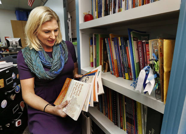 <p>Teacher Mackinley Cross looks at books on Wednesday in Moore. Cross and three colleagues teamed up to offer free professional development to teachers from cash-strapped school districts. [Photo by Steve Sisney, The Oklahoman]</p>