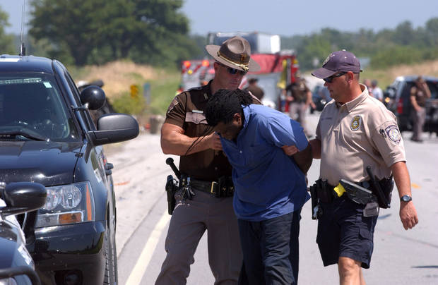 photo - Attempted bank robbery suspect in custody following fatal high-speed chase north of Quapaw, Okla. on 69a Hwy.  The suspect was found by OHP airplane hiding in some weeds not far from the crash scene.   Gary Crow/For the Oklahoman