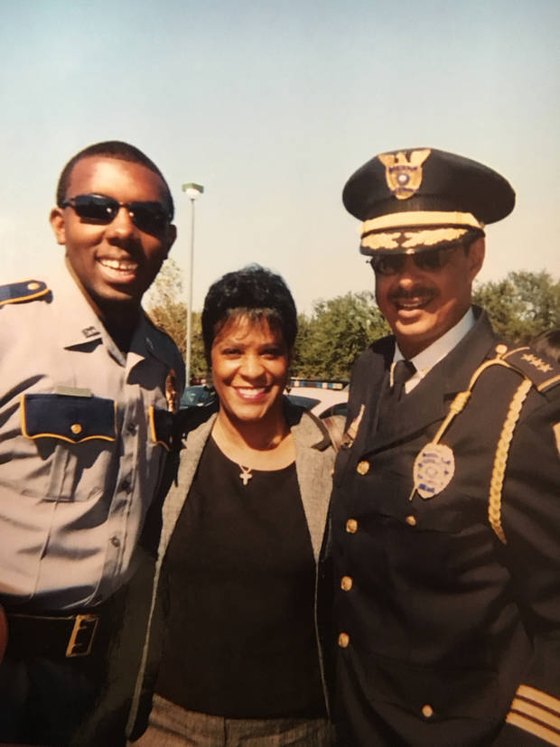 In this undated photo provided by Trenisha Jackson, her husband, Baton Rouge Police Officer Montrell Jackson, from left, his aunt Darlene Cavalier and former Baton Rouge Police Chief Jeff LeDuff pose for a photo at a graduation ceremony to become a police officer in Baton Rouge, La. Montrell Jackson and two other Baton Rouge law enforcement officers investigating a report of a man with an assault rifle were killed Sunday, July 17, 2016, less than two weeks after a black man was fatally shot by police here in a confrontation that sparked nightly protests that reverberated nationwide. (Courtesy of Trenisha Jackson via AP)