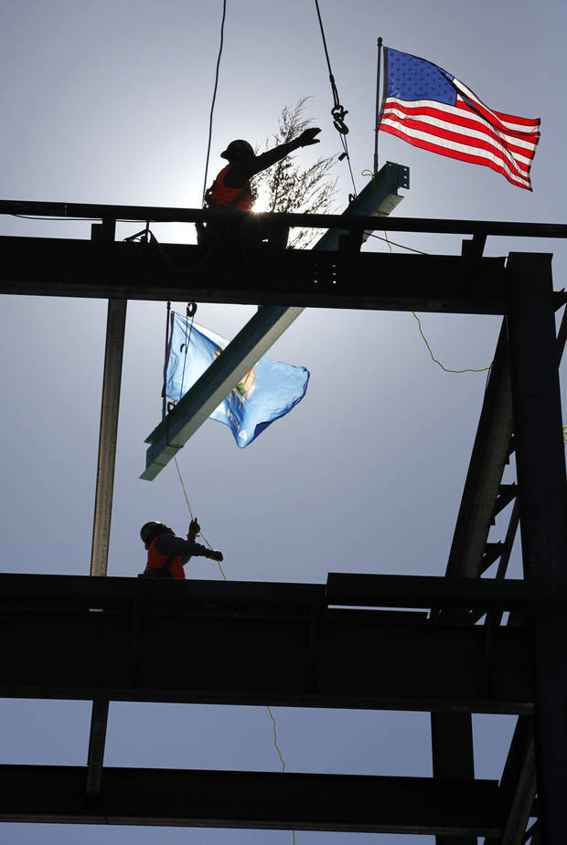 Sept. 24, 2010: Eberardo Ballesteros, bottom, and Mario Nunez guide the last beam in place during the topping out ceremony for Intergris Health in Edmond. [Photo by Steve Gooch, The Oklahoman Archives]