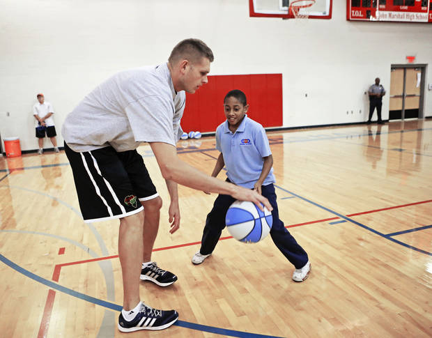 photo - Thunder player Cole Aldrich plays basketball with Colby Gill, 12, during a Thunder Fit clinic at John Marshall High School in Oklahoma City, Wednesday, September 19, 2012. Photo by Bryan Terry, The Oklahoman