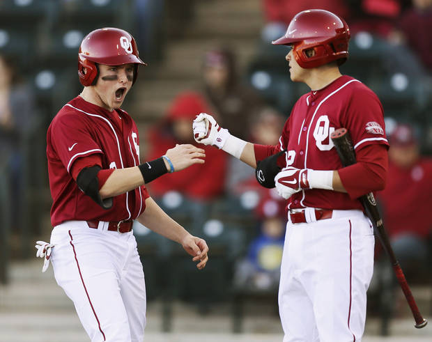 photo - Oklahoma's Craig Aikin (3), left, celebrates with Hector Lorenzana (12) after scoring in the fifth inning during OU's season-opening college baseball game against Seton Hall at L. Dale Mitchell Park in Norman,  Okla., Friday, Feb. 14, 2014. Photo by Nate Billings, The Oklahoman