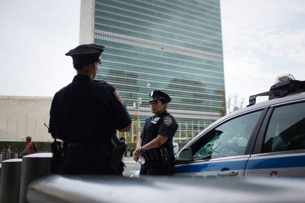Officers keep watch across the street from United Nations Headquarters Sunday, Sept. 18, 2016, in New York. Security is tightened after an improvised bomb was detonated in a dumpster Saturday night in the Chelsea section of the New York City. (AP Photo/Kevin Hagen)