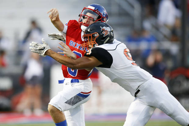 Bixby's Mason Williams gets hit by Booker T. Washington's Krishawn Brown during the football game between the Bixby Spartans and the Booker T Washington Hornets at Lee Snider Field on Friday, September 28, 2018. IAN MAULE/Tulsa World