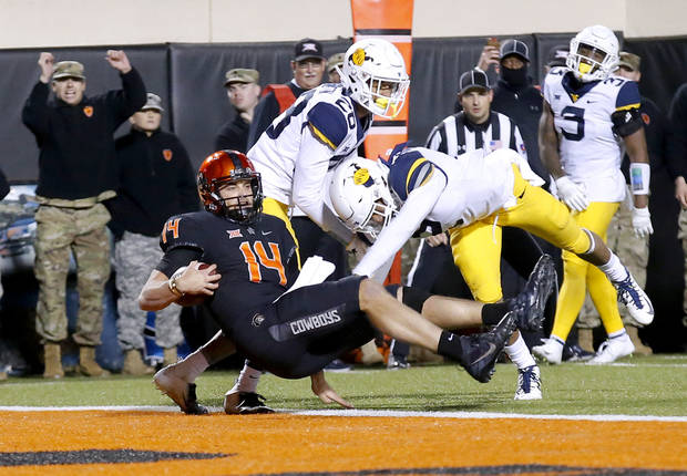 Taylor Cornelius (14) and Oklahoma State face a high-scoring Mizzou squad in the Liberty Bowl on New Year's Eve in Memphis, Tenn. [Photo by Sarah Phipps, The Oklahoman]