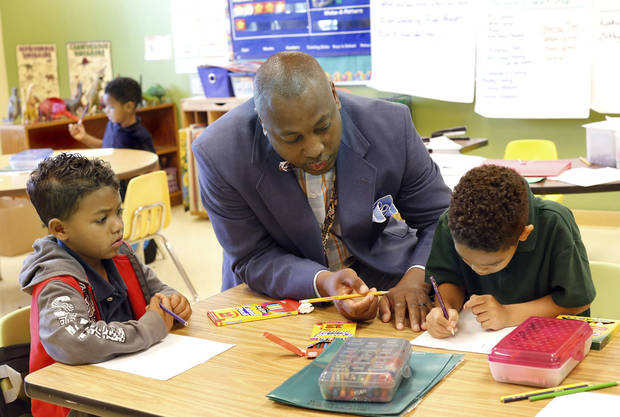 Kindergarten teacher Harold Smith stops at one of several small tables in his classroom to help a student with a daily assignment, this one being about shapes of objects. For story that looks at the lack of male teachers, especially black male teachers. in Oklahoma City elementary schools. Kelly Coleman, principal at Green Pastures Elementary School in Spencer has hired a few black male teachers to be part of the school's faculty. Photo by Jim Beckel, The Oklahoman