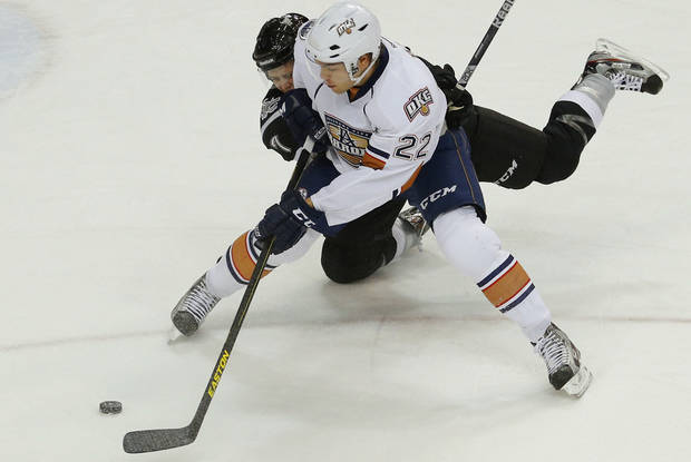 photo - Tanner House of the Oklahoma City Barons shoots the puck around John Lee of the San Antonio Rampage during an AHL hockey game at the Cox Convention Center in Oklahoma City, Friday, Dec. 28, 2012. Photo by Bryan Terry, The Oklahoman