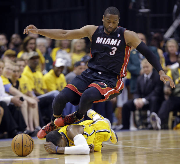 photo - Miami Heat guard Dwyane Wade (3) goes over Indiana Pacers forward Paul George as they went for a loose ball during the fourth quarter of Game 2 of the NBA basketball Eastern Conference finals in Indianapolis, Tuesday, May 20, 2014. The Heat defeated the Pacers 87-83 to tie the series at 1-1. (AP Photo/Michael Conroy)